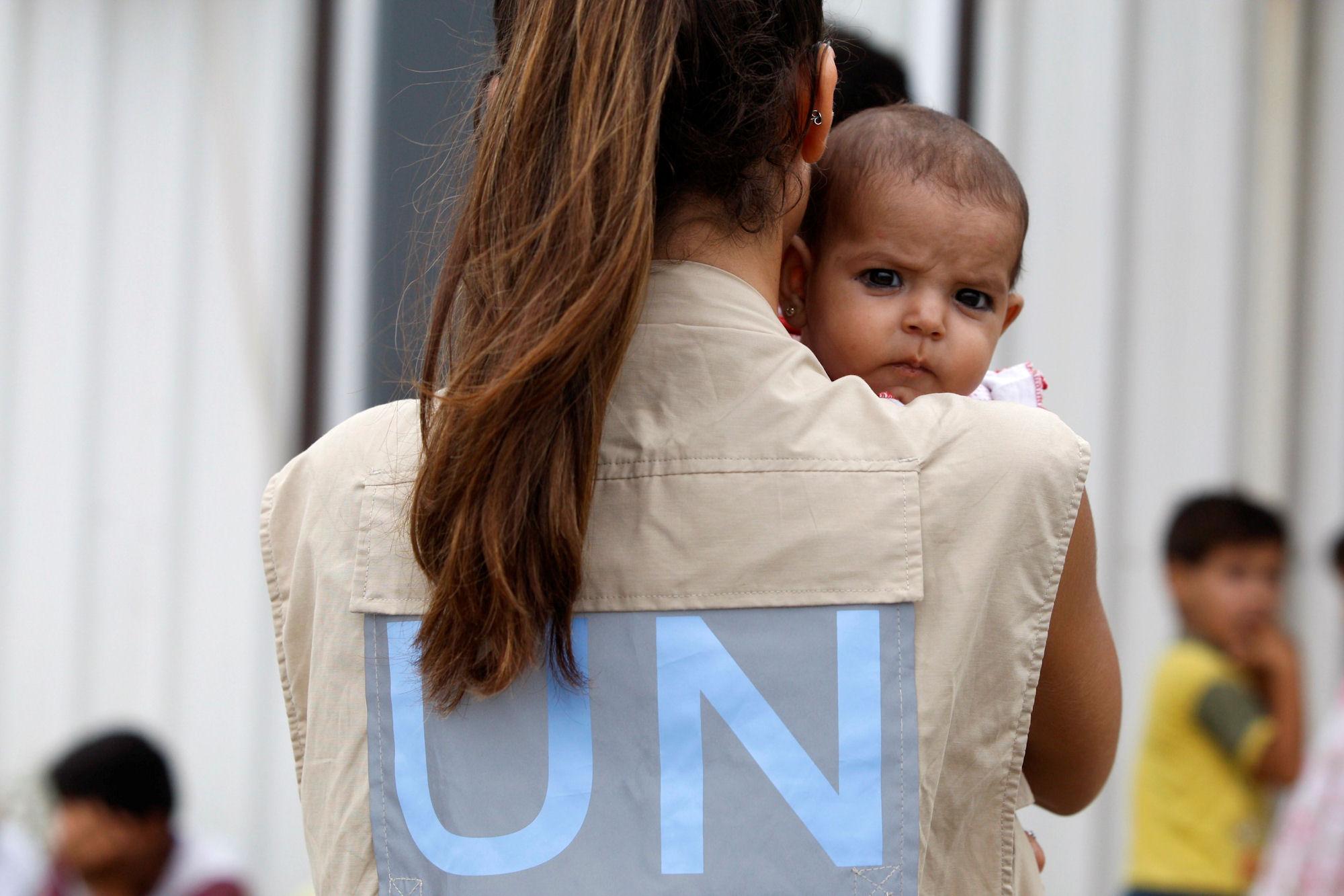 UNHCR-Mitarbeiterin kümmert sich um das Baby syrischer Flüchtlinge, während sich die Eltern registrieren lassen - Al Beereh/Libanon. (© UNHCR/S. Malkawi)