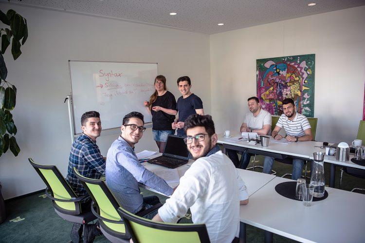 Deutschunterricht bei NETZWERK-Mitglied proLogistik: die Azubis Mohamad Habra, Zabihollah Khodadady, Fittahi Salah, Muhamed Ali Abdulaziz und Mohamed Ali Natoura (v.l.n.r.), Softwareentwickler Adnan Awad (hinten Mitte) und Lehrerin Bettina Kliebisch.