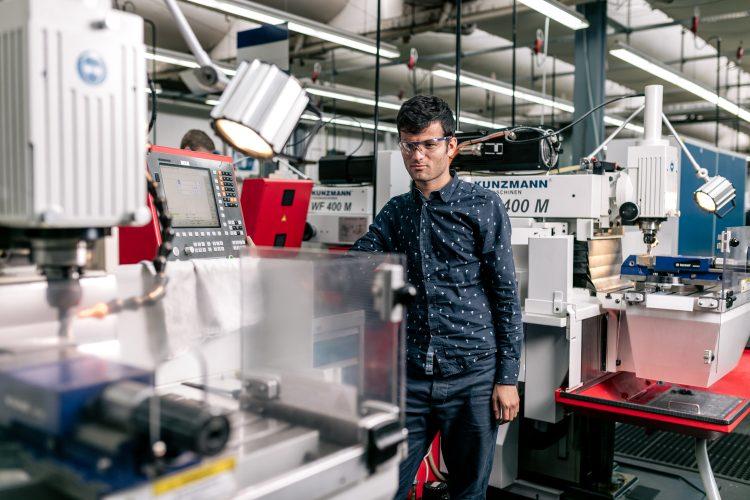 Ein junger Mann steht an einer Maschine